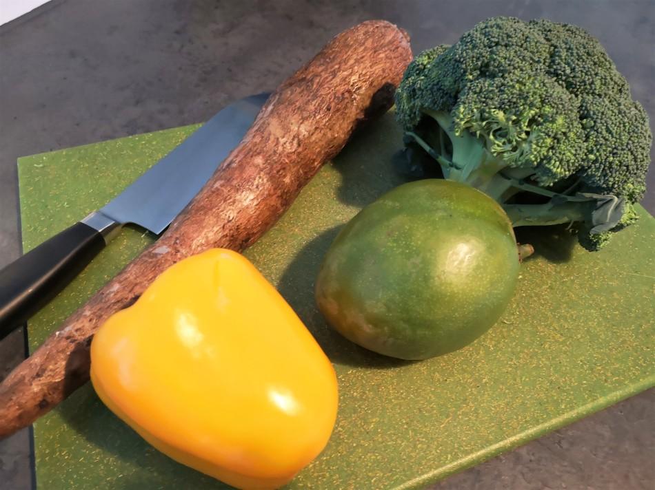 Maniokwurzel, Mango, Brokkoli und gelbe Paprika liegen auf einem grünen Schneidbrett.