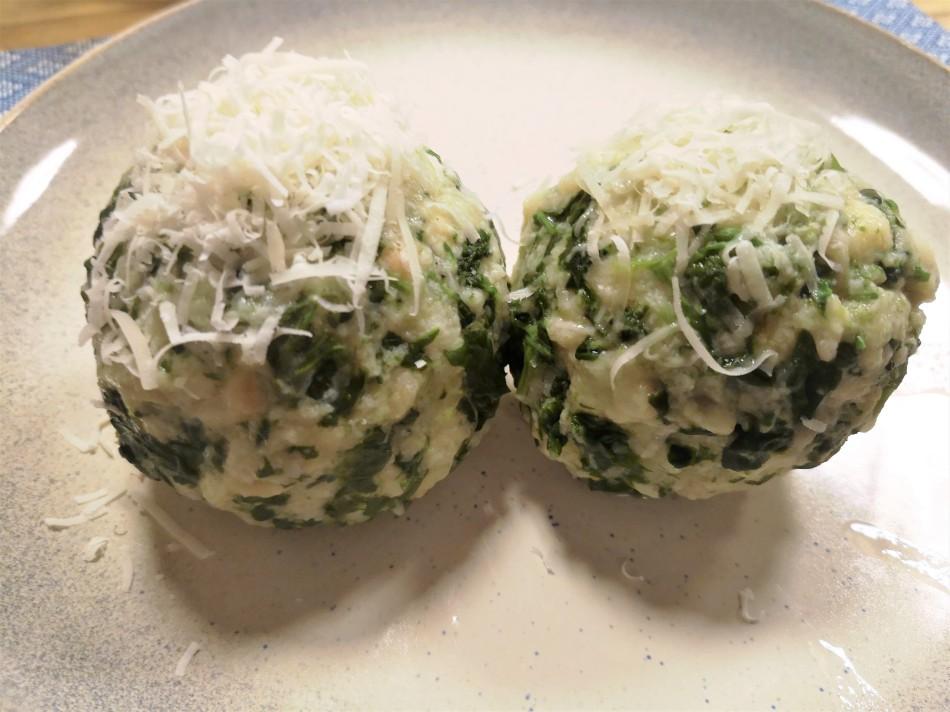 Zwei Spinatknödel mit geriebenen Käse